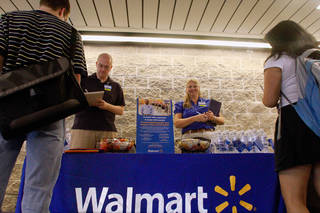 Walmart employees Jon Christians and Lori Harris take job applications and answers questions during a job fair at the University of Illinois Springfield campus in Springfield, Ill. AP Photo