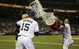 San Diego Padres' Jesus Guzman tries to hide behind sideline reporter Kelly Crull as teammate Everth Cabrera throws a bucket of water at him following Guzman's game-winning hit in the 17th inning of the Padres' 4-3 victory over the Toronto Blue Jays in a baseball game in San Diego, Saturday, June 1, 2013. (AP Photo/Lenny Ignelzi) ORG XMIT: CALI134