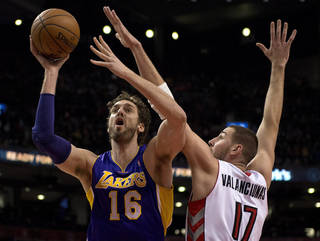 Los Angeles Lakers center Pau Gasol (16) drives to the hoop past Toronto Raptors center Jonas Valanciunas during first-half NBA basketball game action in Toronto, Sunday, Jan. 19, 2014. (AP Photo/The Canadian Press, Frank Gunn)