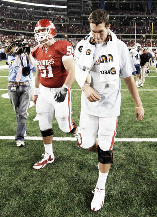 Oklahoma quarterback Sam Bradford, right, walks off the field next to Brian Lepak on Saturday after OU lost to Brigham Young University at Cowboys Stadium in Arlington, Texas. PHOTO By Nate Billings, The Oklahoman
