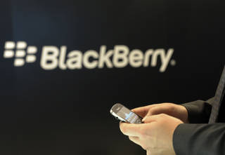 A BlackBberry employee holds a mobile phone of BlackBerry in Berlin. AP Photo