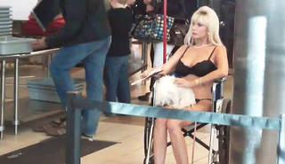 Tammy Banovac, 52, clad in undergarments and sitting in a wheelchair, failed to pass the Transportation Security Administration screening process Tuesday when security officers detected traces of nitrates on her wheelchair. Frame grab from video by John Maringouin