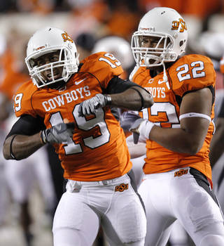 Oklahoma State's Brodrick Brown (19) and James Thomas (22) celebrate after Brown's interception during the Bedlam college football game between the University of Oklahoma Sooners (OU) and the Oklahoma State University Cowboys (OSU) at Boone Pickens Stadium in Stillwater, Okla., Saturday, Nov. 27, 2010. Photo by Chris Landsberger, The Oklahoman