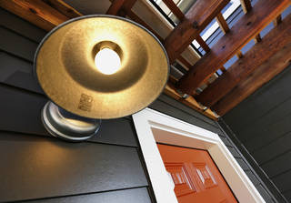 A brass porchlight cover and red door set off the entry to a house at 1212 NW 16 completed and sold earlier this month by Positively Paseo. Photo by Jim Beckel, The Oklahoman Jim Beckel -