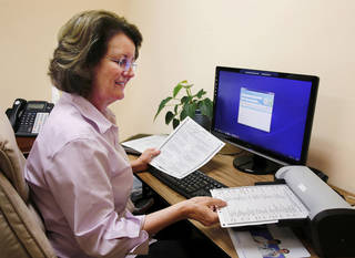 Debi Willis, founder and chief executive of PatientLink, demonstrates how the product works, using a scanner and sophisticated software to capture and upload data collected on paper questionnaires completed by patients. Photo by Jim Beckel, The Oklahoman Jim Beckel