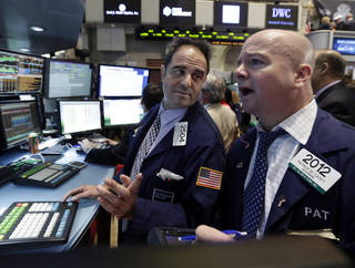 Specialist Jorge Fernandez, left, and trader Patrick Casey, work Thursday on the floor of the New York Stock Exchange. U.S. stocks are rising in early trading, helped by strong earnings from Facebook and a report that the U.S. economy grew at an annual rate of 3.2 percent in the fourth quarter. AP Photo - AP