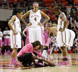 From left, Oklahoma's Gioya Carter (25), Nicole Griffin (4), Morgan Hook (10) and Sharane Campbell (24) watch athletic trainer Carolynn Loon attend to Aaryn Ellenberg (3) after she was injured in the second half during the women's Bedlam college basketball game between the OU Sooners and the OSU Cowgirls at Gallagher-Iba Arena in Stillwater, Okla., Sunday, Feb. 16, 2014. OSU won, 73-57. Photo by Nate Billings, The Oklahoman