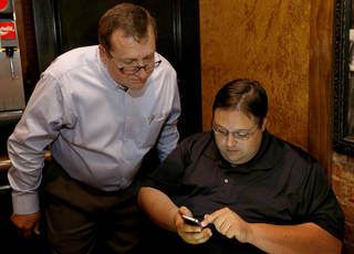 Mark McBride checks results with John Roberts, right, at a watch party for House District 53 on Tuesday at the Two Olives Cafe in Moore. Photo by Sarah Phipps, The Oklahoman SARAH PHIPPS