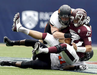 Oklahoma State's Caleb Lavey (45) and Shaun Lewis (11) bring down Mississippi State's Tyler Russell (17) during first half of the AdvoCare Texas Kickoff college football game between the Oklahoma State University Cowboys (OSU) and the Mississippi State University Bulldogs (MSU) at Reliant Stadium in Houston, Saturday, Aug. 31, 2013. Photo by Sarah Phipps, The Oklahoman