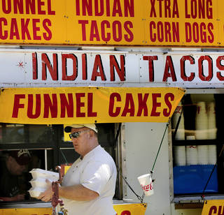 A man walks away with boxes of Indian tacos he purchased during the Indian powwow at Joe B. Barnes Regional Park in Midwest City. Photo by Jim Beckel, The Oklahoman Jim Beckel -