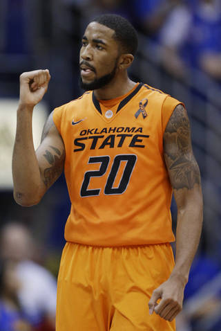 Oklahoma State forward Michael Cobbins celebrates a lead during the second half of an NCAA college basketball game against Kansas in Lawrence, Kan., Saturday, Feb. 2, 2013. Oklahoma State won 85-80. (AP Photo/Orlin Wagner) ORG XMIT: KSOW112