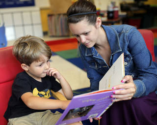 Cooper Stephens, 4, and his mom, Johnna Kirkland, look at a book Thursday in the pre-K room at Wilson Elementary in Oklahoma City. Photo by Sarah Phipps, The Oklahoman SARAH PHIPPS -