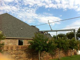 A metal utility pole snapped in the wind and damaged this house at NW 164 and Stillmeadows Drive. Photo by Robert Medley