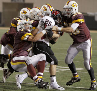 A group of Clinton defenders including Payne Veazey, left, and Trey Mckinsey try yo bring down Wagoner's Devin Hawkins in the class 4A state championship high school football game at Boone Pickens Stadium in Stillwater, Okla., Friday, Dec. 2, 2011. Photo by Bryan Terry, The Oklahoman