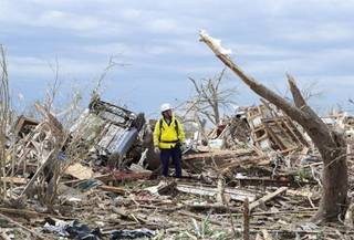 A recovery worker surveys the destruction in a neighborhood in Moore, Oklahoma May 21, 2013. Scientist warnings that Oklahoma may be hit by a major earthquake has caused a run on insurance policities in the state, adding to woes of residents already hit by earthquakes. REUTERS/Richard Rowe