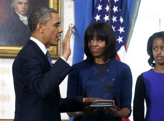 President Barack Obama is officially sworn-in by Chief Justice John Roberts, not pictured, in the Blue Room of the White House during the 57th Presidential Inauguration in Washington, Sunday, Jan. 20, 2013, as first lady Michelle Obama, holds the Robinson Family Bible, and daughter Malia watches. (AP Photo/Larry Downing, Pool) ORG XMIT: WX312