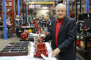 KIMRAY CEO Tom Hill poses with gas regulators in Oklahoma City, Monday August 19, 2013. Photo By Steve Gooch, The Oklahoman