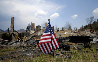 A United States flag is planted near one of the homes destroyed by the Waldo Canyon Fire in the Mountain Shadows neighborhood of Colorado Springs, Colo., on Monday, July 2, 2012. So far, the blaze, now 45 percent contained, has damaged or destroyed nearly 350 homes. (AP Photo/Bryan Oller) ORG XMIT: COBO102