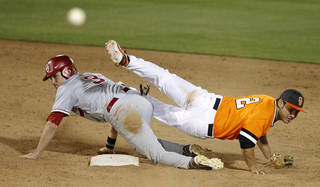 OSU's Tim Arakawa trips over OU's Craig Aikin after throwing from second to complete a double play in the 14h inning of a Bedlam baseball game between Oklahoma State University and the University of Oklahoma in Stillwater, Tuesday, April 15, 2014. Photo by Bryan Terry, The Oklahoman