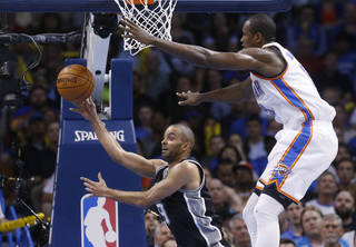 San Antonio Spurs guard Tony Parker (9) passes off from under the net in front of Oklahoma City Thunder forward Serge Ibaka (9) in the second quarter of an NBA basketball game in Oklahoma City, Thursday, April 3, 2014. (AP Photo/Sue Ogrocki)