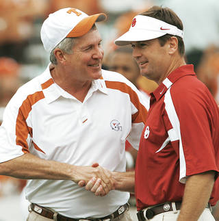 Texas coach Mack Brown, left, and Oklahoma coach Bob Stoops shake hands before the 2007 Red River Rivalry game. Berry Tramel says that by going into the Pac-10 together, the Big 12 schools would have strength in numbers. Photo By Steve Sisney, The Oklahoman Archive