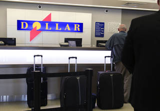 In this May 9, 2011 file photo, customers wait in line at a Dollar rental car counter at San Jose International Airport in San Jose, Calif. More than two years after its original bid, Hertz agreed Sunday to buy Dollar Thrifty Automotive Group Inc. for about $2.3 billion, giving it more ways to attract travelers and expand its international presence. It will also give the company a leg up against competition from an increasing number of smaller competitors. AP PHOTO Paul Sakuma - AP