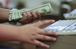 A cashier rings up a cash sale at a Sears store in Las Vegas in November. U.S. consumers borrowed more in November to buy cars and attend school, but stayed cautious with their credit cards, the Federal Reserve said Tuesday. AP PHOTO Julie Jacobson - AP