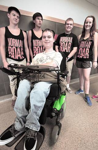 """Norman High School senior Jake Pyle poses with students wearing """"Norman Roar"""" T-shirts, which were sold to help fund a music video contest entry that features Pyle. David McDaniel - The Oklahoman"""