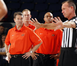 Oklahoma State coaches Travis Ford, left, and Butch Pierre, right ,get an explanation on a foul call during the second half of an NCAA college basketball game at the 76 Classic in Anaheim, Calif., Friday, Nov. 26, 2010. (AP Photo/Christine Cotter)