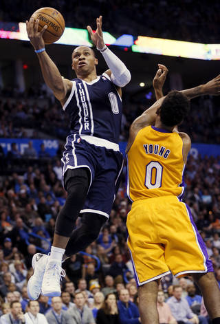 Oklahoma City's Russell Westbrook (0) takes the ball past LA's Nick Young (0) during an NBA basketball game between the Los Angeles Lakers and the Oklahoma City Thunder at Chesapeake Energy Arena in Oklahoma City, Friday, Dec. 13, 2013. Photo by Nate Billings, The Oklahoman