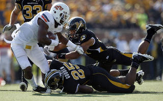 Oklahoma State running back Joseph Randle, left, runs for an 18-yard gain as Missouri's Matt White and Zaviar Gooden (25) defend during the first half of an NCAA college football game Saturday, Oct. 22, 2011, in Columbia, Mo. (AP Photo/Jeff Roberson)