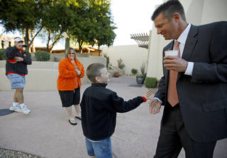 Seven-year-old Michael Bruce, of Canton, Ga., slaps hands with Oklahoma State coach Mike Gundy as his parents Jeremy and Courtney Bruce watch after a Fiesta Bowl press conference in January. Gundy and his players have been showered with appreciation by fans since winning their first Big 12 Conference title and BCS bowl. Photo by Bryan Terry, The Oklahoman.