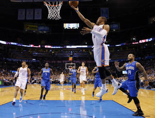 Oklahoma City's Russell Westbrook, center, shoots a layup in front of Orlando's Jameer Nelson during Sunday's game. Photo by Sarah Phipps, The Oklahoman
