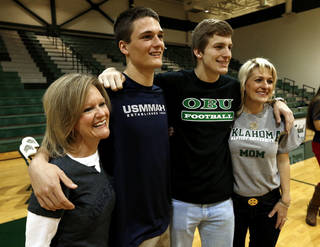 Channing Meyer and his mother Liz Meyer, left, and Corbin Cleveland and his mother Christina Cleveland pose for photographs after a signing day assembly at Norman North High School on Wednesday, Feb. 6, 2013, in Norman, Okla. Meyer will play for the Merchant Marine Academy and Cleveland will play for Oklahoma Baptist University. Photo by Steve Sisney, The Oklahoman
