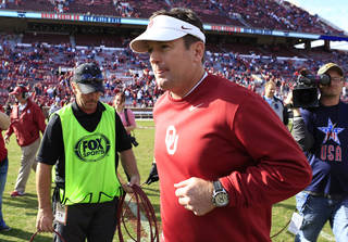 Oklahoma head coach Bob Stoops runs to the locker room after defeating Iowa State 48-10 in an NCAA college football game in Norman, Okla. on Saturday, Nov. 16, 2013. (AP Photo/Alonzo Adams)