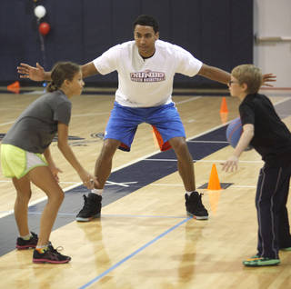 Oklahoma City Thunder forward Josh Huestis works with students as he visits this week's Thunder Youth Basketball camp at Casady School in Oklahoma City, OK, Thursday, July 17, 2014, Photo by Paul Hellstern, The Oklahoman
