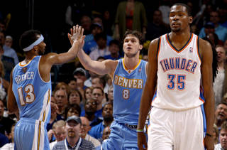 Denver's Danilo Gallinari (8) and Corey Brewer (13) celebrate beside Oklahoma City's Kevin Durant during the NBA basketball game between the Oklahoma City Thunder and the Denver Nuggets at Chesapeake Energy Arena in Oklahoma City, Wednesday, April 25, 2012. Oklahoma City lost 106-101. Photo by Bryan Terry, The Oklahoman