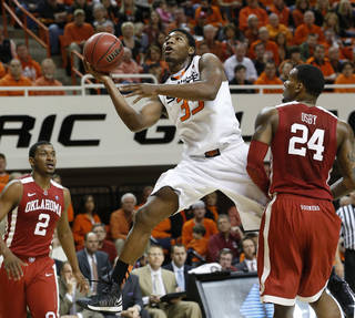 Oklahoma State guard Marcus Smart (33) shoots between Oklahoma guard Steven Pledger (2) and forward Romero Osby (24) in the first half of an NCAA college basketball game in Stillwater, Okla., Saturday, Feb. 16, 2013. (AP Photo/Sue Ogrocki) ORG XMIT: OKSO101