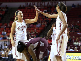 Oklahoma guard Nicole Kornet, left and Nicole Griffin, right, celebrate over Maryland Eastern Shore guard Mariah McCoy, center, after a play during the first half of an NCAA women's college basketball game in Norman, Okla., Sunday, Dec. 15, 2013. (AP Photo/Alonzo Adams)