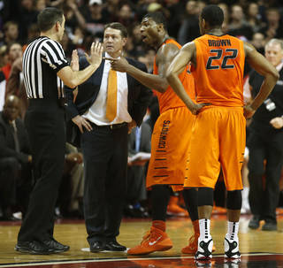 Oklahoma State head coach Travis Ford, center, Marcus Smart and Markel Brown(22) speak to the referee after Smart shoved a fan during a NCAA college basketball game in Lubbock, Texas, Saturday, Feb, 8, 2014. (AP Photo/Lubbock Avalanche-Journal, Tori Eichberger)