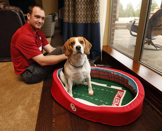 Kevin Kruger and his dog, Miss Dixie Mae, show one of the pet beds he designed and sells Thursday in Norman. STEVE SISNEY - THE OKLAHOMAN