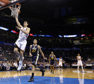 Oklahoma City 's Steven Adams (12) dunks in front of Utah's Rudy Gobert (27) during the NBA game between the Oklahoma City Thunder and the Utah Jazz at the Chesapeake Energy Arena, Sunday, March 30, 2014, in Oklahoma City. Photo by Sarah Phipps, The Oklahoman