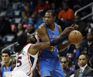 Atlanta Hawks forward DeMarre Carroll (5) reaches for the ball as he defends Oklahoma City Thunder forward Kevin Durant in the first half of an NBA basketball game Tuesday, Dec. 10, 2013, in Atlanta. (AP Photo/John Bazemore)
