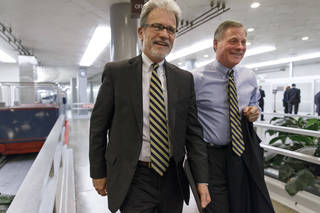 Sen. Tom Coburn, left, R-Muskogee, walks with Sen. Richard Burr, R-N.C., on the way to a procedural vote on a comprehensive defense bill Thursday at the Capitol in Washington. AP PHOTO