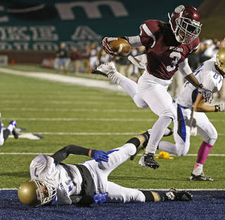 Edmond Memorial's Waylan Anderson leaps over Choctaw's Kennedy Humphrey before the play was called back due to a penalty on Edmond Memorial during their high school football game at Wantland Stadium in Edmond, Thursday, October 17, 2013. Photo by Bryan Terry, The Oklahoman