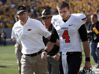 OSU coach Mike Gundy walks off Mountaineer Field at Milan Puskar Stadium with quarterback J.W. Walsh after the Cowboys' 30-21 loss to West Virginia on Saturday. Photo by Sarah Phipps, The Oklahoman
