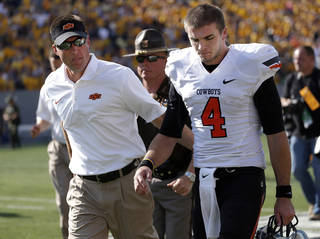 Oklahoma State University coach Mike Gundy walks with J.W. Walsh (4) off the field after the Cowboys loss to West Virginia University on Mountaineer Field at Milan Puskar Stadium in Morgantown, W. Va., Saturday, Sept. 28, 2013. SARAH PHIPPS - The Oklahoman