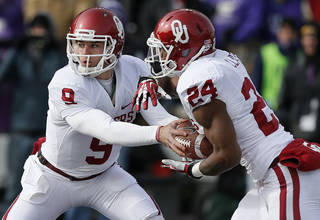 Oklahoma's Trevor Knight (9) hands off to Brennan Clay (24) during an NCAA college football game between the Oklahoma Sooners and the Kansas State University Wildcats at Bill Snyder Family Stadium in Manhattan, Kan., Saturday, Nov. 23, 2013. Oklahoma won 41-31. Photo by Bryan Terry, The Oklahoman