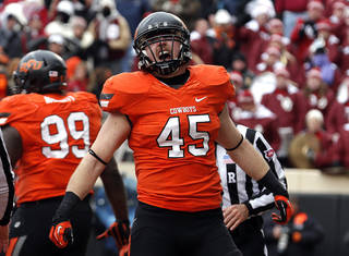 Oklahoma State's Caleb Lavey (45) celebrates a tackle in the fourth quarter during the Bedlam college football game between the Oklahoma State University Cowboys (OSU) and the University of Oklahoma Sooners (OU) at Boone Pickens Stadium in Stillwater, Okla., Saturday, Dec. 7, 2013. OU won 33-24. Photo by Sarah Phipps, The Oklahoman