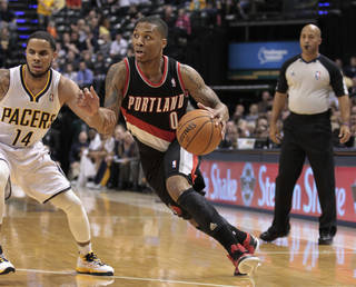 Portland Trail Blazers point guard Damian Lillard, front right, drives past Indiana Pacers point guard D.J. Augustin in the first half of an NBA basketball game in Indianapolis, Wednesday, Dec. 5, 2012. (AP Photo/Michael Conroy) ORG XMIT: NAF106